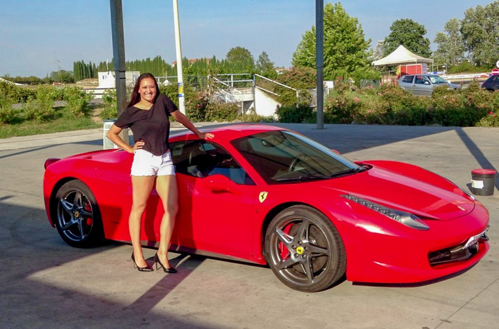 A woman dressed nice in short white shorts, black shirt and high heels next to a red Ferrari to fulfill her Italy bucket list.