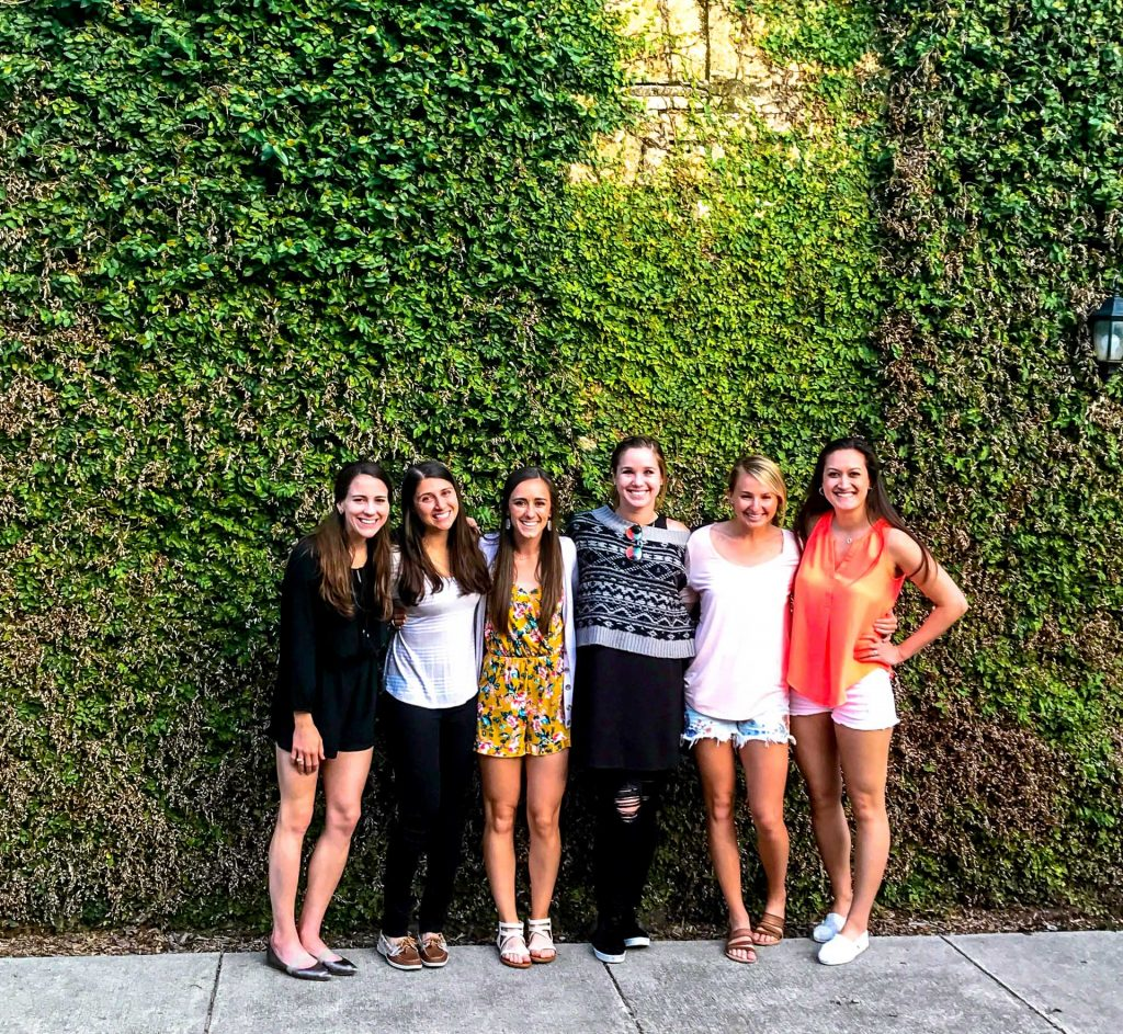 Six girls enjoying their girls weekend in Fredericksburg, Texas, smiling against a wall covered in vines.