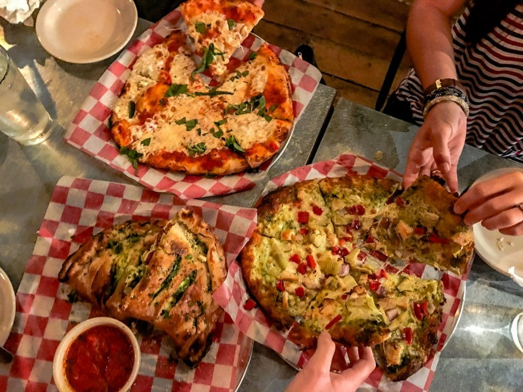 Hands taking a slice from two whole pizzas and a calzone at Woerner Warehouse.