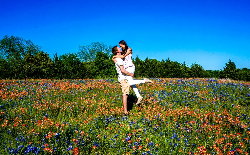 A man picking up his wife in the middle of a wildflower and bluebonnet field in Ennis, Texas.