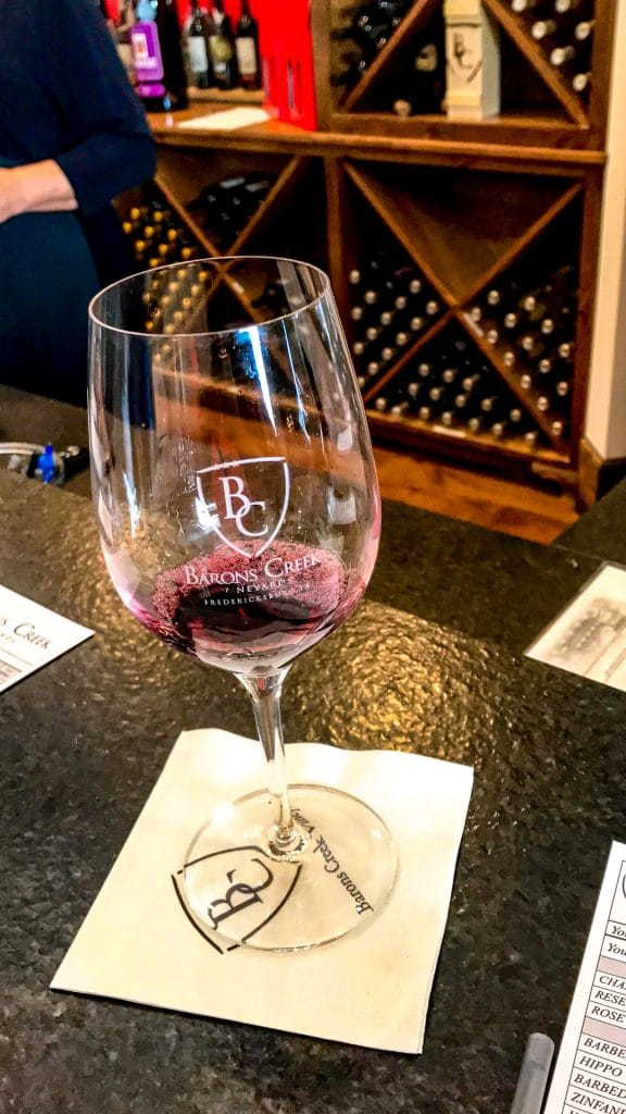A red wine being poured into a glass for a wine tasting at Barons Creek Vineyard.