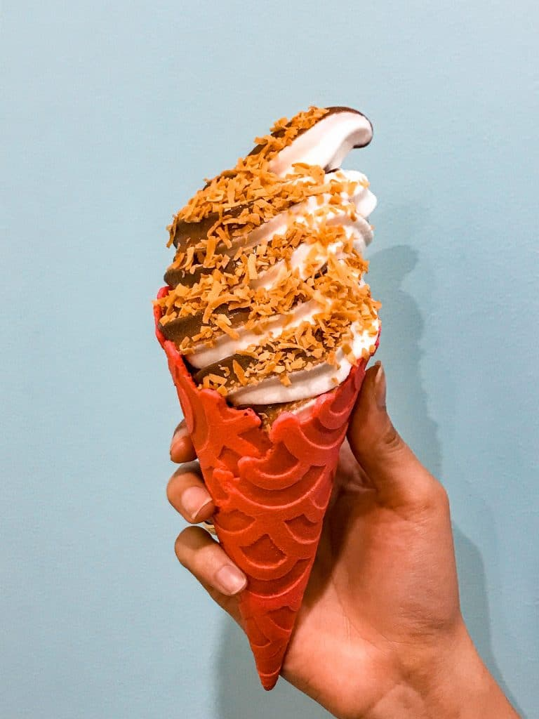 A swirl of chocolate and coconut soft serve ice cream inside a red waffle cone from Sugar Pine Creamery in Plano.