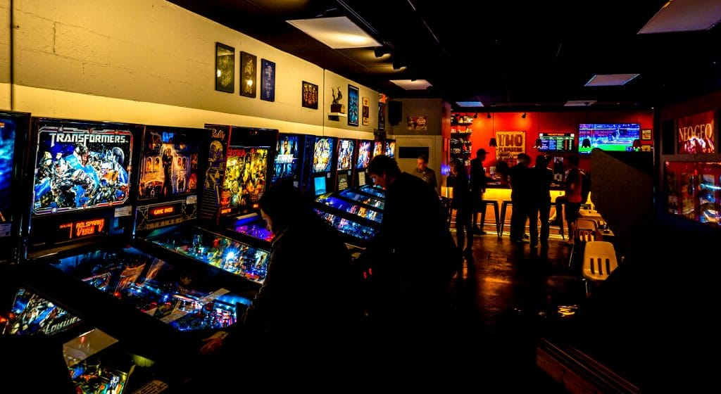 A dark room with people playing classic pinball machines at Two Plumbers Arcade and Brewery.