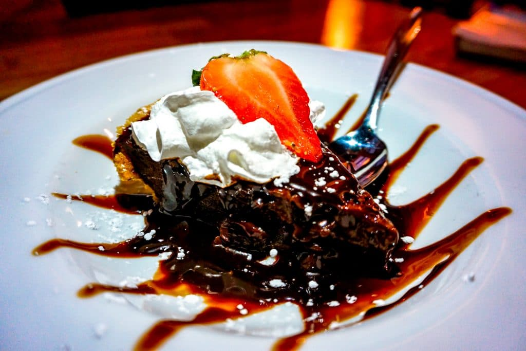 A mouthwatering plate of hot fudge pie with whipped cream and a strawberry on top from Didi's Downtown.