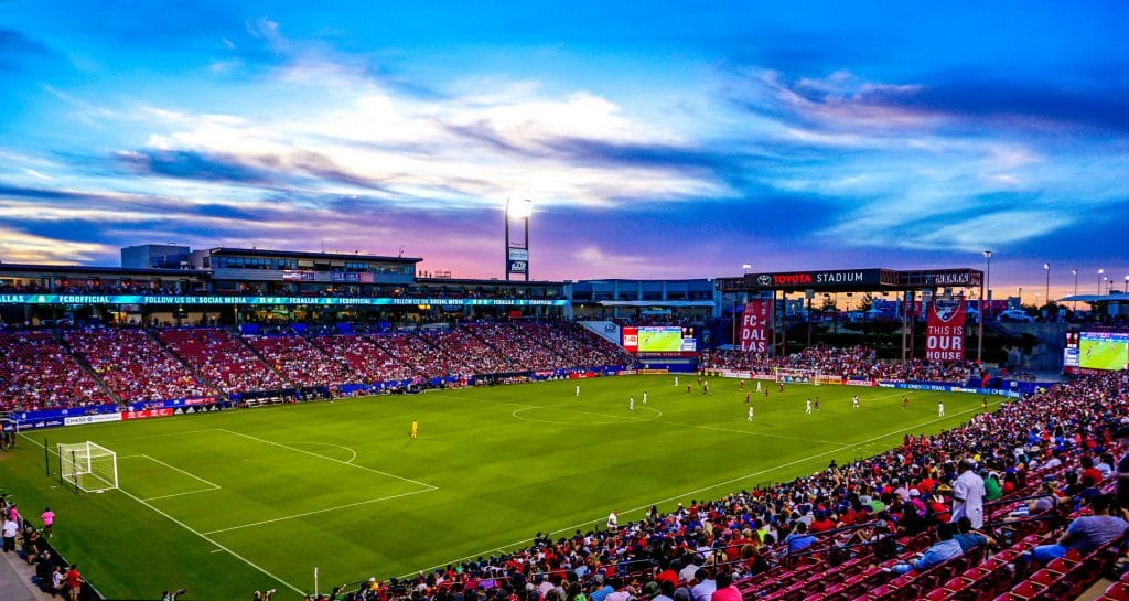 Stunning sunset photo of the FC Dallas soccer game at Toyota Stadium in Frisco with shades of deep blue and purple in the sky.