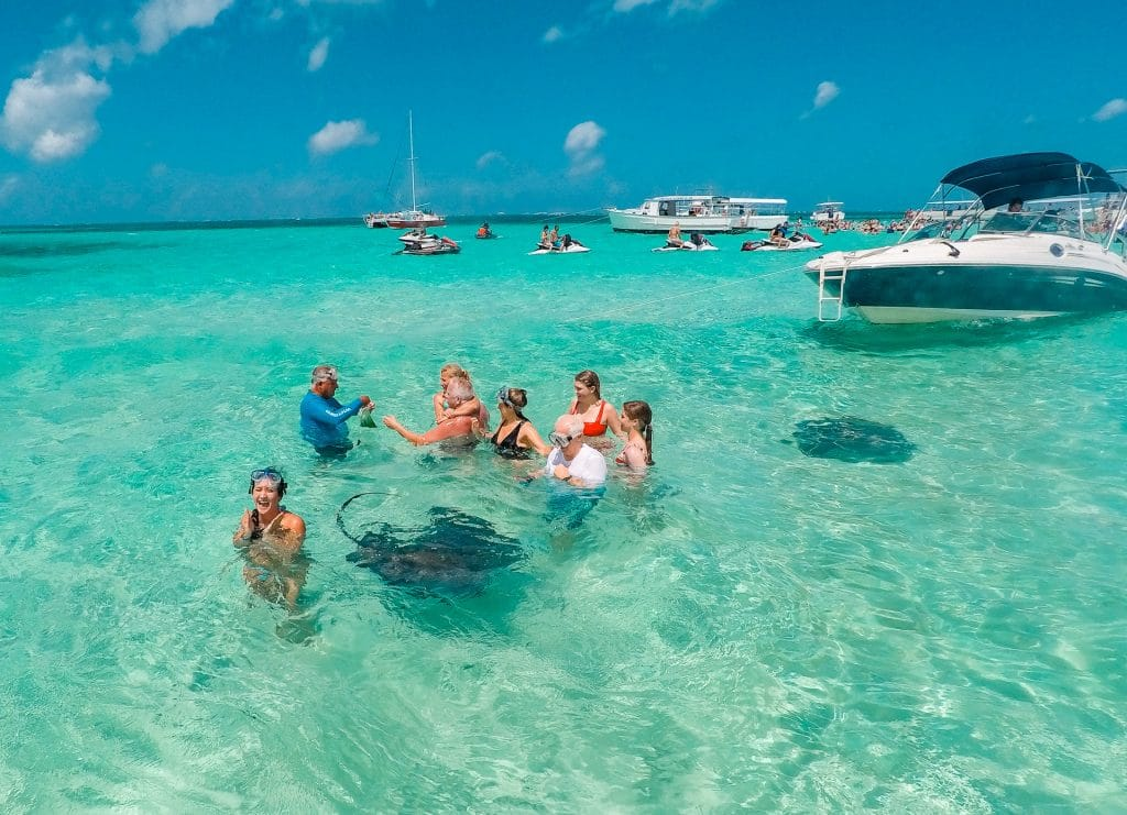 a group of people standing in shallow water with stingrays swimming nearby. There are also more people and boats in the background.