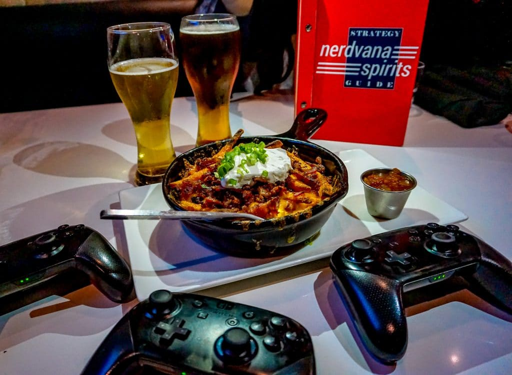A table with three black Switch controllers,  a skillet of loaded fries and two glasses of beer from Nerdvana.