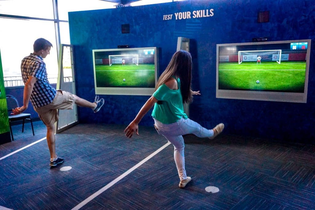 A couple playing with the interactive exhibit kicking a virtual soccer ball at the Soccer Hall of Fame.