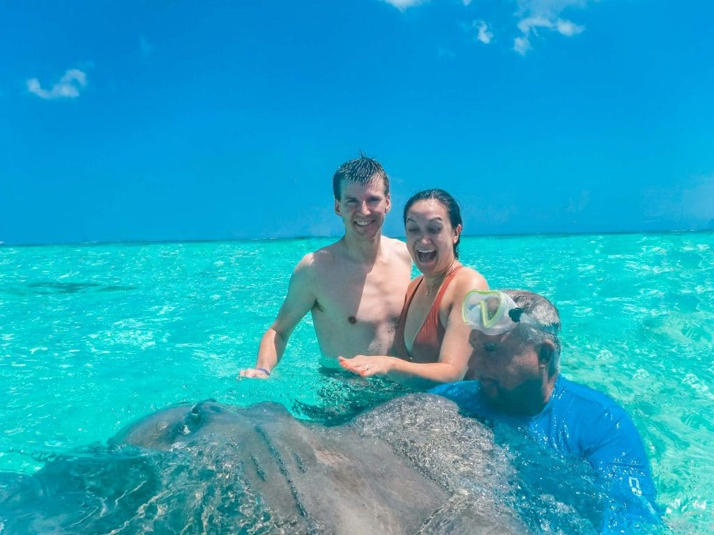 A man and woman stroking a stingray at Stingray City with their tour guide.