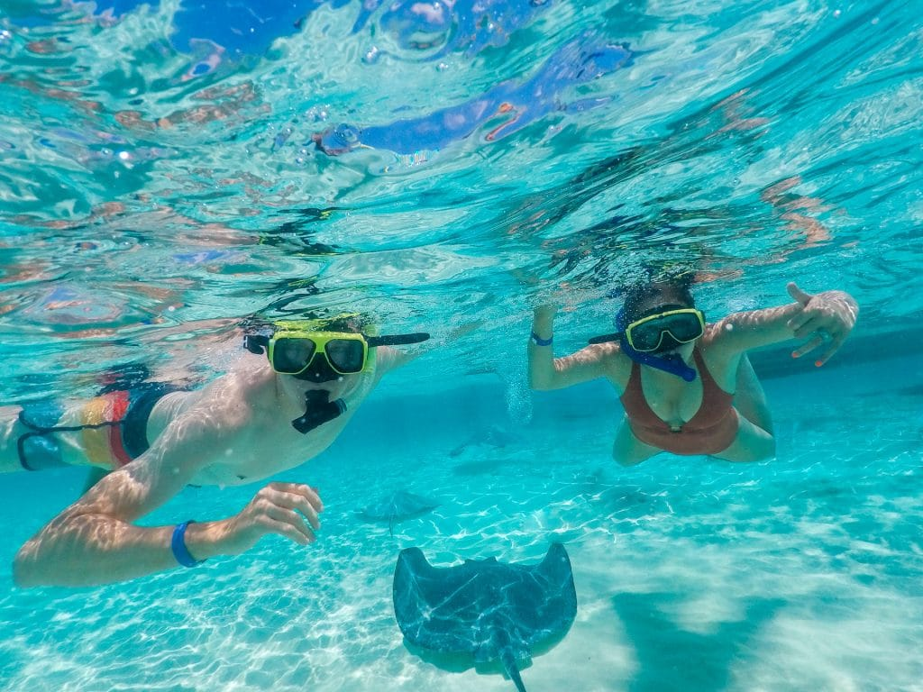 A man and woman swimming with stingrays in the Grand Cayman.