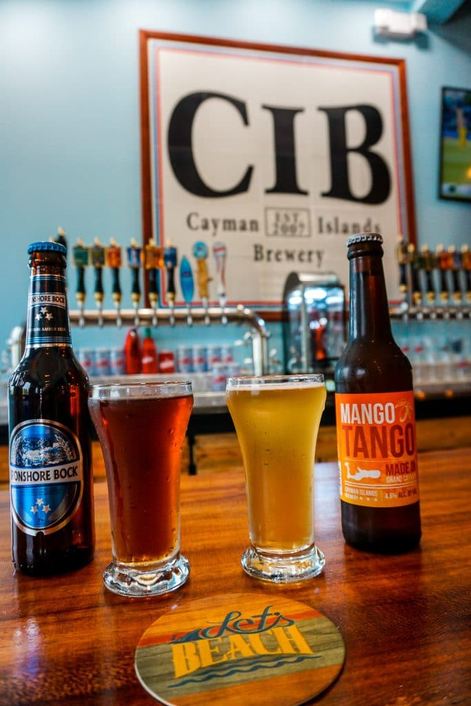 two glasses and bottles of beer on a wooden bar top with Cayman Islands Brewery logo in the background.