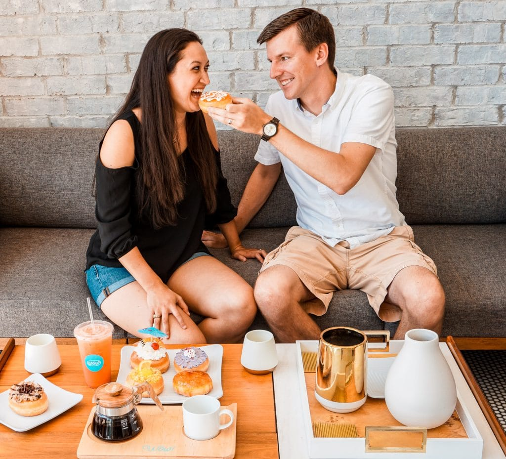 A man feeding a woman an orange glazed donut. The table in front of them has coffee, tea, and a plate full of donuts.