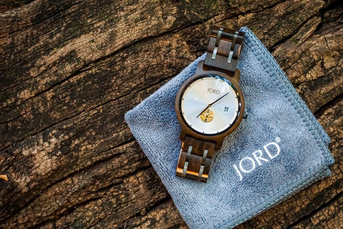A JORD Hyde wooden watch on top of a gray square cloth resting on a wooden log.