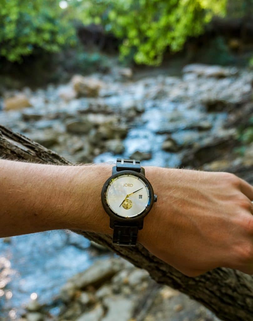 A man's arm in the center of the photo representing a wooden watch from JORD with a stream of water in the background.