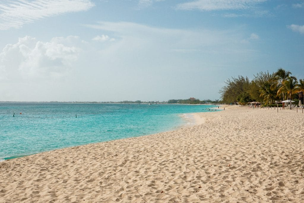 A pristine white sand beach with the ocean on the left in shades of blue and trees in the distance.