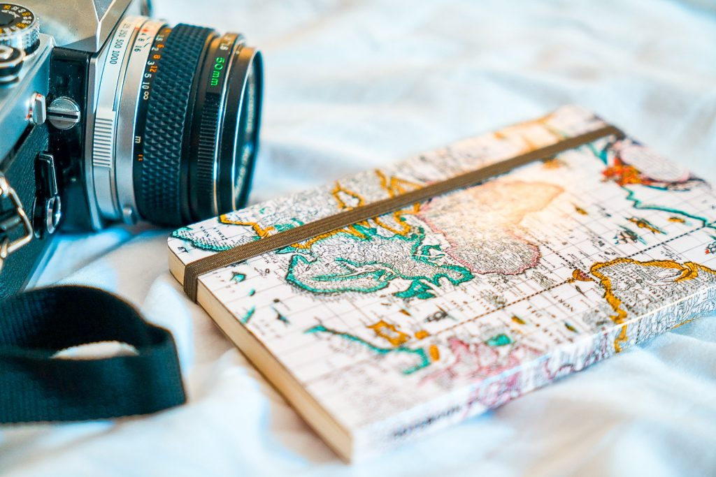 A notebook with the map as the cover and a camera next to it.