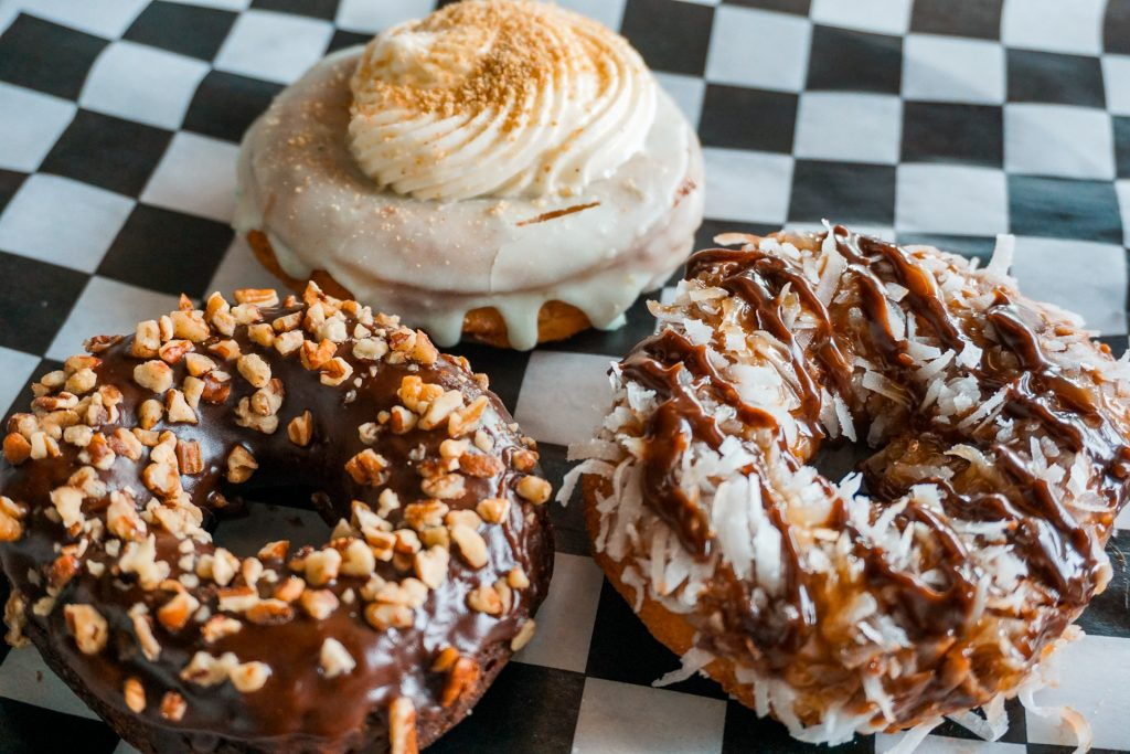 A picture of some of the best donuts in Dallas from The Donut Kitchen. A Texas Sheet Cake, Key Lime, and Caramel Coconut donut.