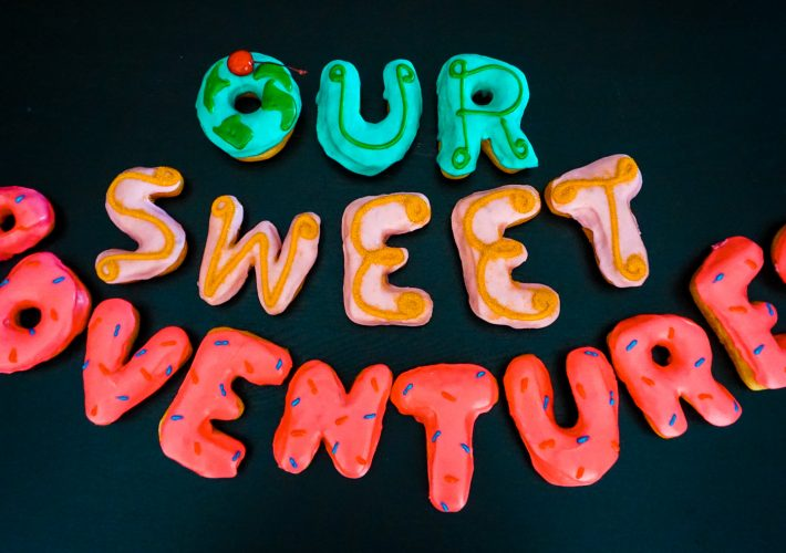 "Donuts that spell out ""Our Sweet Adventures""."