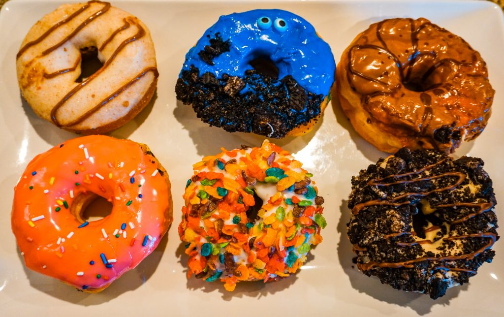 A variety of six of the best donuts in Dallas from Hurts Donuts. There are donuts with cinnamon sugar, a blue donut with chocolate cookie crumbs, a caramel icing, pink icing with sprinkles, Fruity Pebbles, and chocolate cookies covered on top.