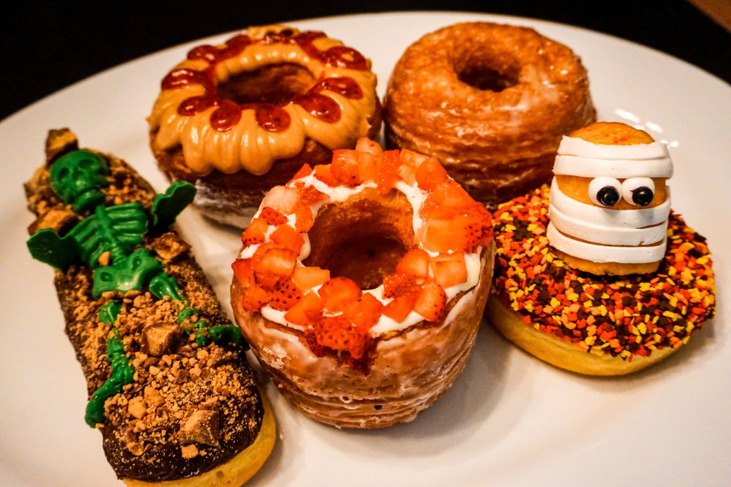 A plate full of some of the best donuts in Dallas. These scrumptious looking donuts include croissant donuts covered in peanut butter and jelly, and strawberries. Then there are Halloween decorated donuts that have a Twinkie mummy and a green skeleton. These donuts can be found at Jarams Donuts.