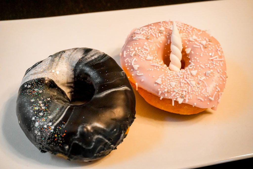 A black and white galaxy with sparkly sprinkles and a pink donut with unicorn horn on top of yeast donuts from Sweet Daze Dessert Bar.