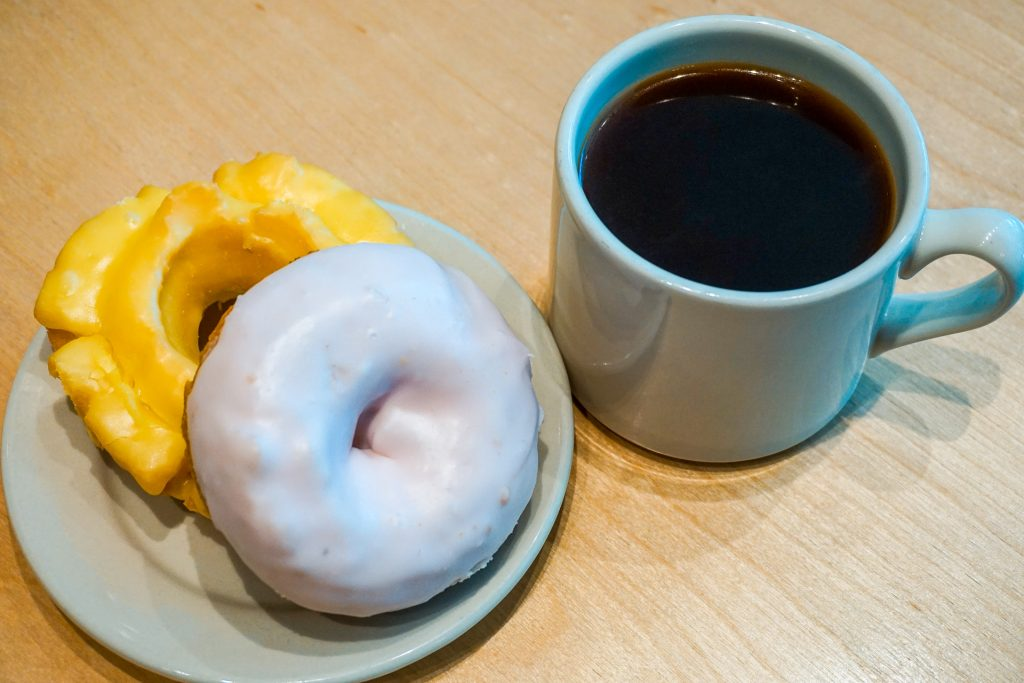 A blueberry cake donut stacked on top of a lemon ol-fashioned donut with a cup of black coffee from Top Pot Doughnuts.