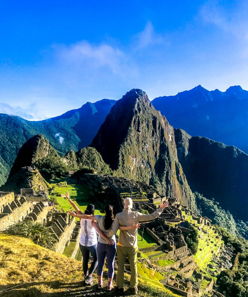 Three people standing with their arms out looking towards Machu Picchu - one of the greatest destinations in the world.