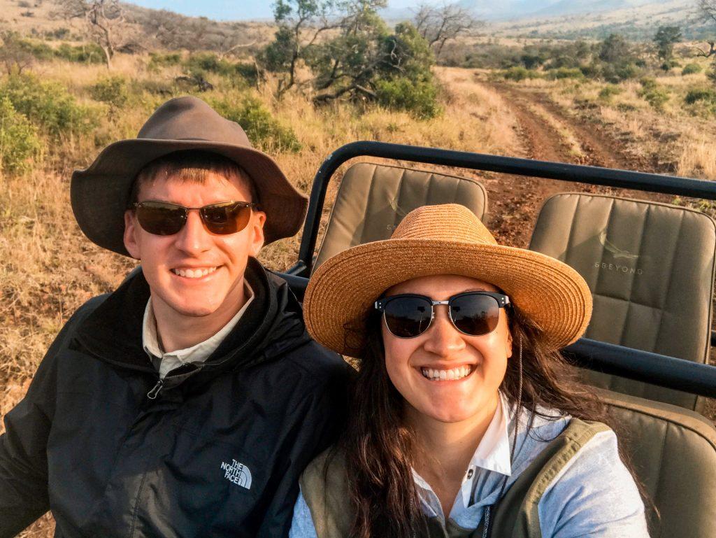 A man and woman riding a jeep enjoying their African safari.