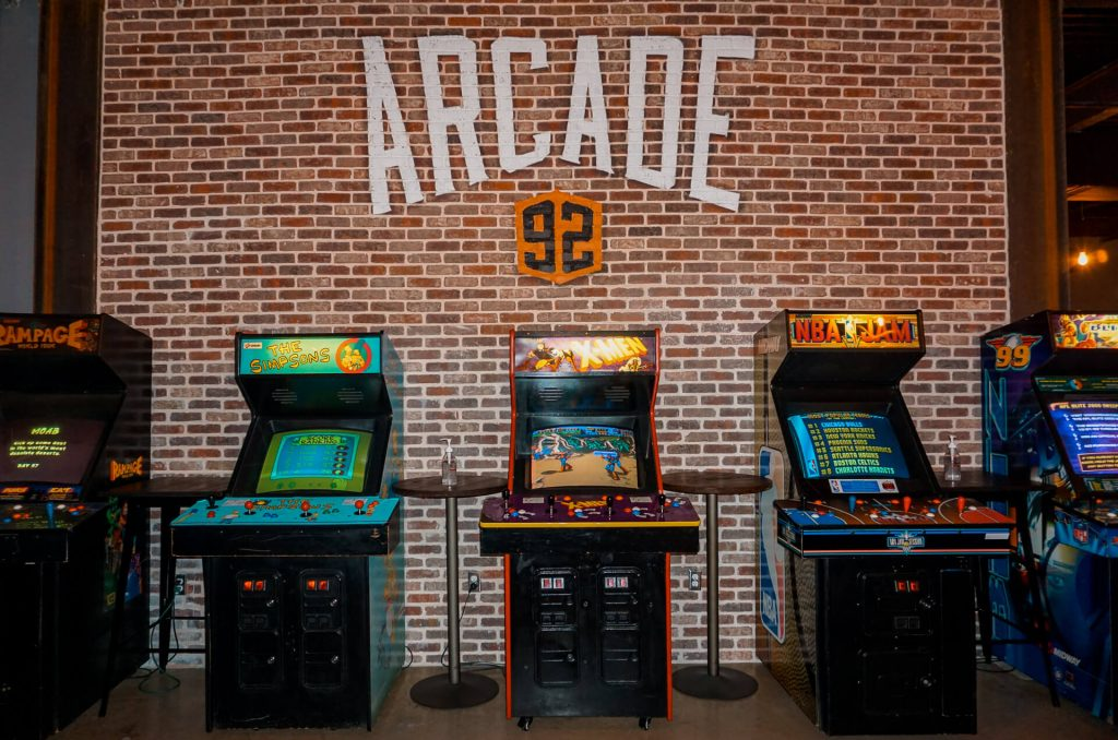 Classic arcade games lines up against a brick wall from Arcade 92 in McKinney, Texas.