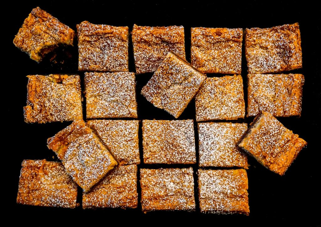 A bird-eye view of Chocolate Peanut Butter Gooey Butter Cake cut in squares displayed in a rectangle and on top of each other.
