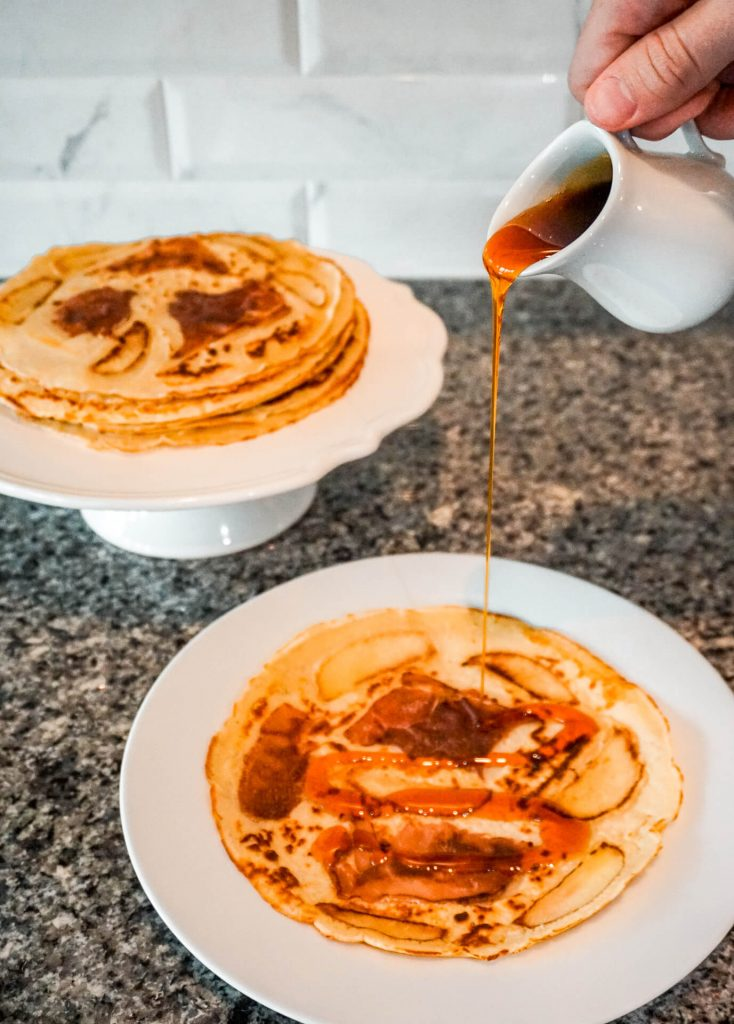 Apple Stroop being poured over Dutch pancakes (pannekoek) with prosciutto and apples.