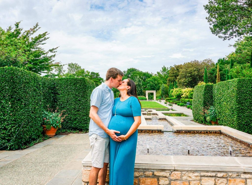 An expecting couple kissing in a beautiful garden at the Dallas Arboretum for their maternity photoshoot.