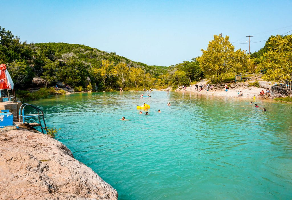 People swimming at Blue Hole Pool at Turner Falls Park in Oklahoma.