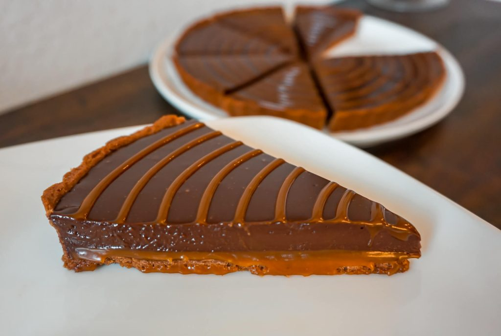 A chocolate caramel tart slice showing a creamy caramel layer on the bottom and a silky smooth chocolate ganache layer on top.