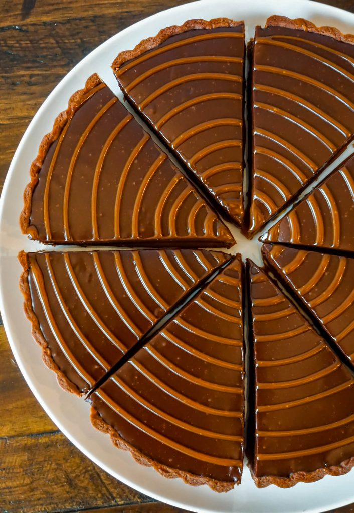Zoomed in photo of chocolate caramel tart slices with caramel drizzled on top.