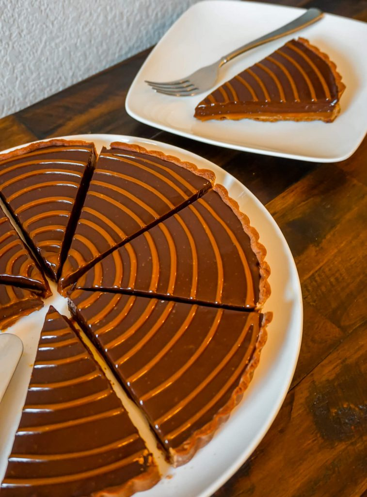 Half of a chocolate caramel tart sliced individually with a plate of one slice in the back.