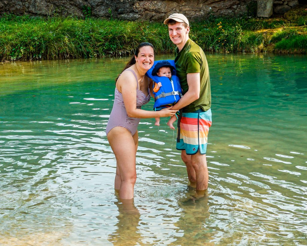 Family holding their baby boy in a life jacket in a swimming hole at Turner Falls Park.