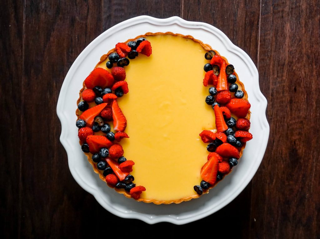 A 9-inch French Lemon Tart (Tarte au Citron) with fresh strawberries, raspberries, and blueberries on top.