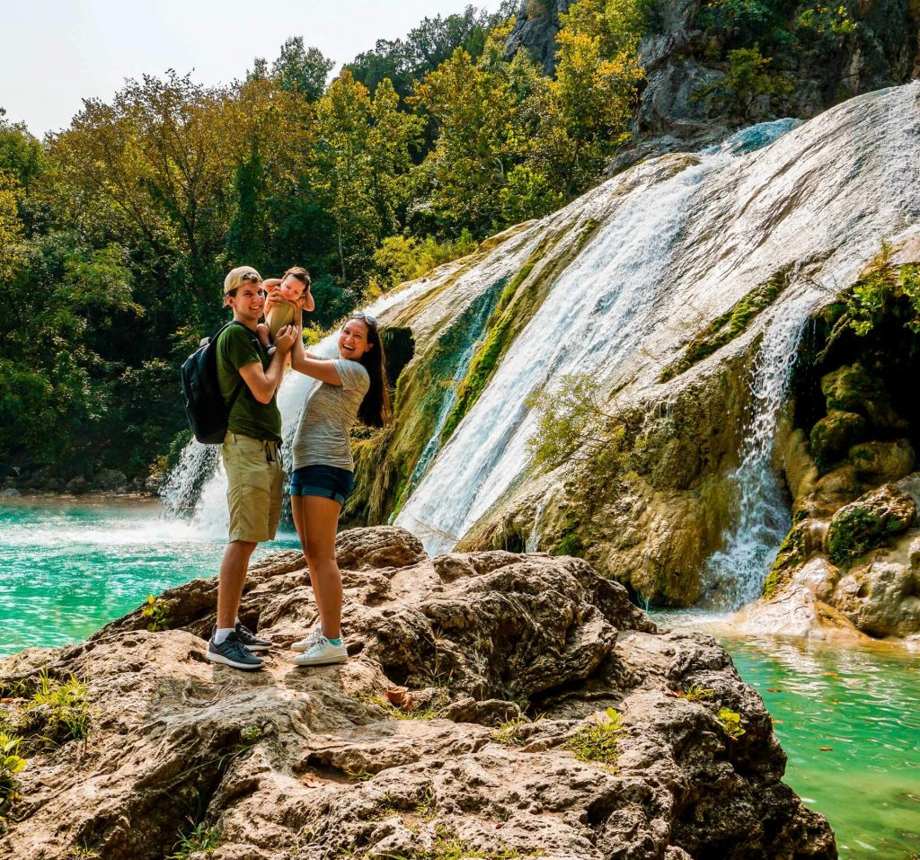 A couple holding up their baby boy on a rock in front of Turner Falls' 77 ft. waterfall.