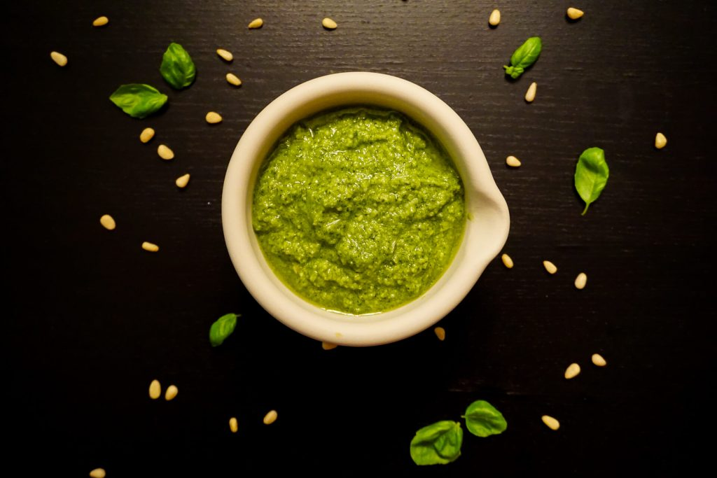 A bowl of bright green pesto with pine nuts and small basil leaves surrounding it.