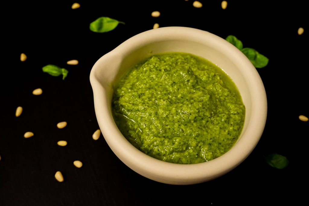 A mortar of homemade pesto with pine nuts and basil leaves around it.