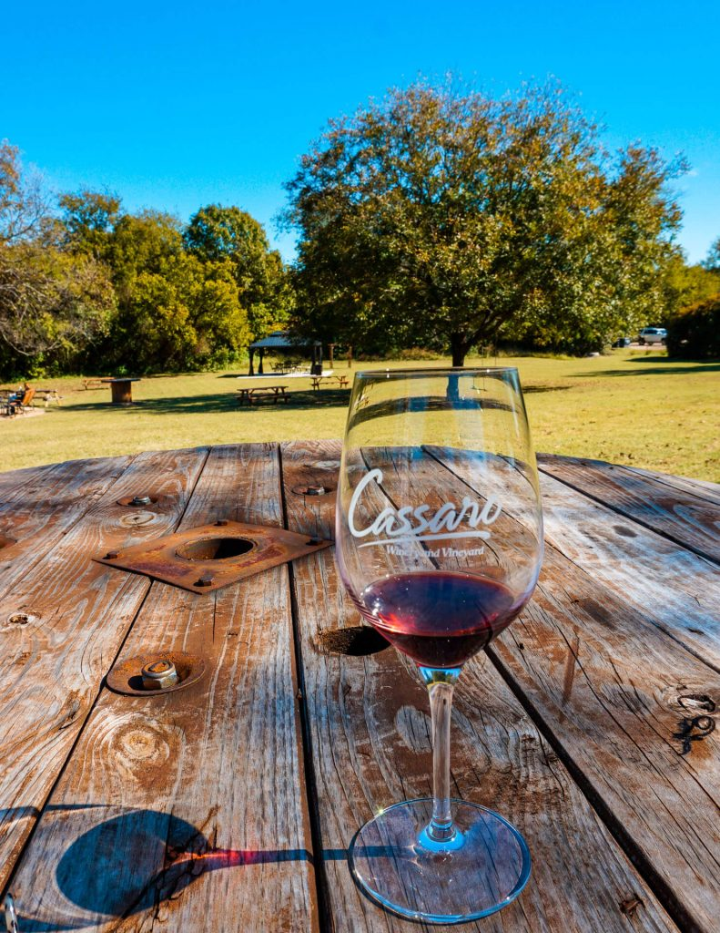 A glass of red wine on a wooden table from one of the best wineries in North Texas, Cassaro Winery and Vineyard.