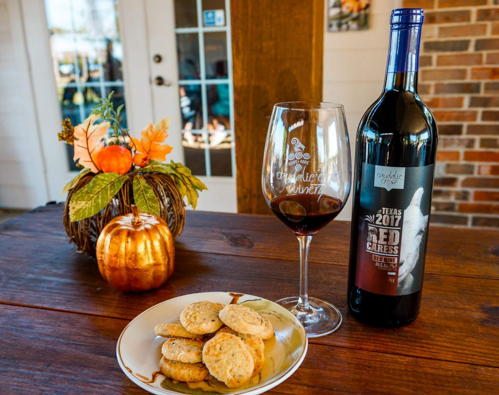 Decorative pumpkins, a plate of Sue's savory shortbread cookies, a glass of red wine, and a bottle of wine from Caudalie Crest Winery & Vineyard in Celina, Texas.