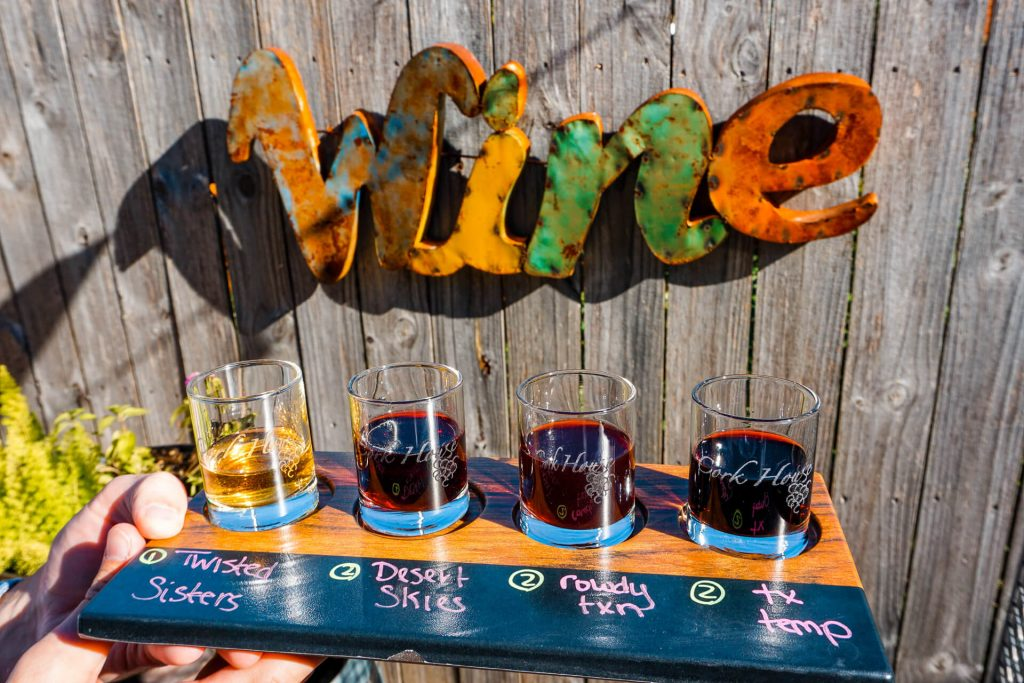 A wine flight from Cork House in front of a Wine sign on a wooden fence.