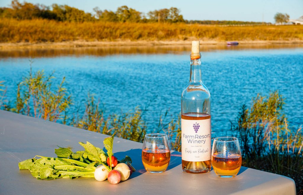 Fresh radishes and turnips alongside two glasses of wine and a wine bottle from FarmResort Winery in front of a peaceful lake.