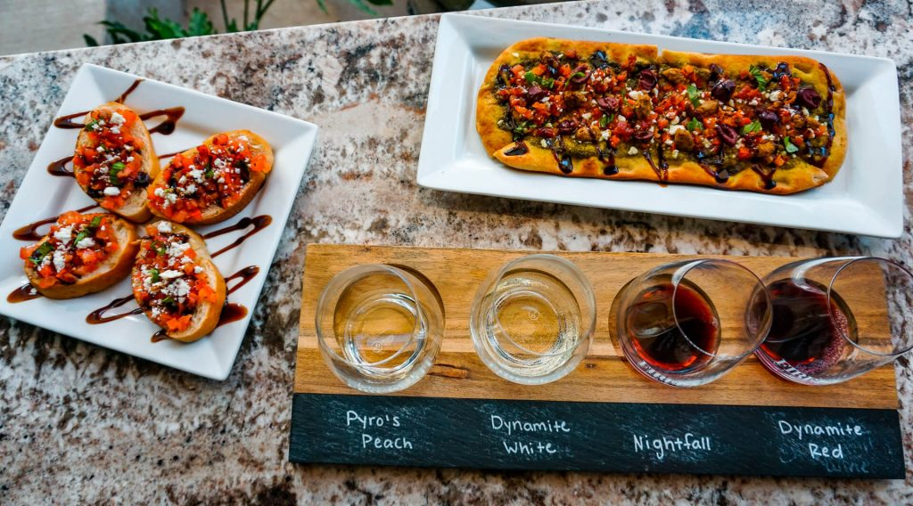 A birds-eye view of a wine flight, plate of bruschetta, and a plate of Sicilian flatbread from Firelight Vineyards - one of the best wineries in North Texas.