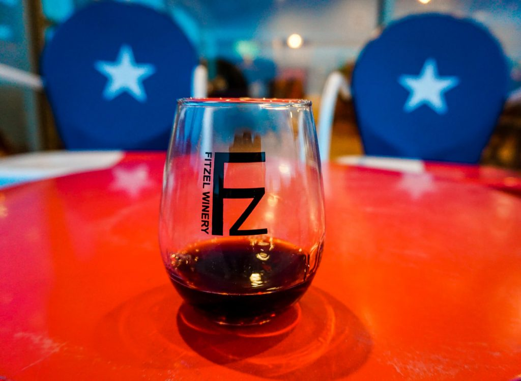 A glass of red wine in a stemless glass from Fitzel Winery with two chairs in the background with the Texas star.