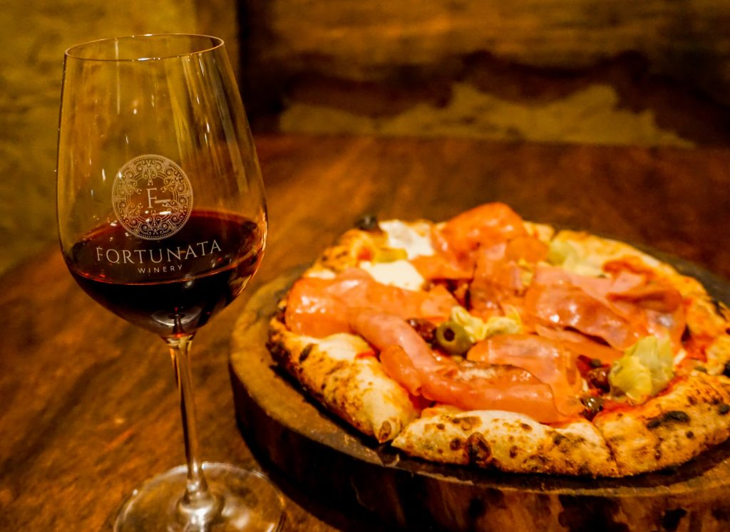 A glass of red wine and a wood-fired pizza from Fortunata Winery.