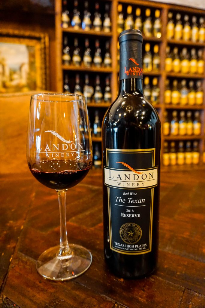 "A bottle of Landon Winery's trademarked ""The Texan"" alongside a glass of red wine."