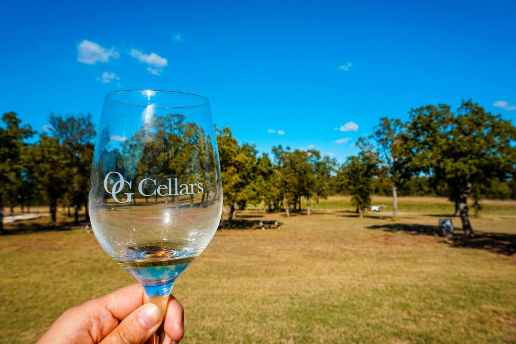 A glass of white wine from OG Cellars with a vast field of trees.